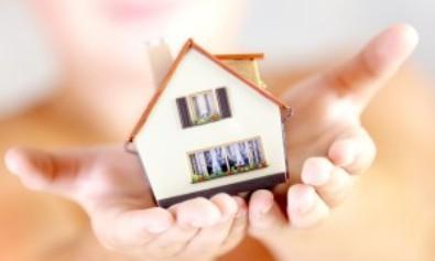 Mains jointes portant une maison